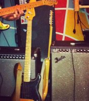 The band's gear includes guitars, basses, and Fender amps.
