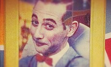 A smirking Pee-wee Herman listens to the band practice.