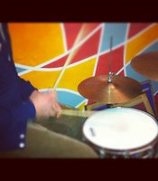 Sam keeps the beat on a customized Donkeys drum set.