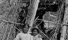 Carolina Leto and son under granary basket, San Ignacio Village, April 9, 1904.  Los Coyotes Reservation, Cahuilla and Cupeno Indians.
