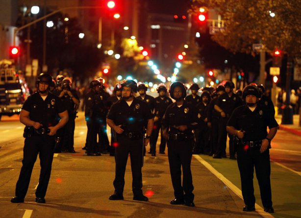 Los Angeles Police Department officers keep watch along a street near to the Occupy LA tent encampment outside City Hall in the early hours of November 30, 2011 in Los Angeles California.