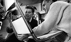 Ray and Charles Eames examining the sling locations to be covered by fabric lapping in a prototype of the Aluminum Group Lounge Chair, 1957.
