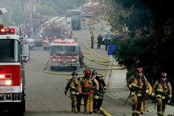 Firefighters head to battle a fire after an FA-18 military jet crashed in a r...