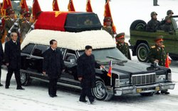 The heir in North Korea, Kim Jong Un, in the black clothes at the front of the vehicle, walks besides the hearse carrying the body of his father and late leader Kim Jong II at Kumsusan Memorial Palace in Pyongyang on Dec. 28. This photo was released by the (North) Korean Central News Angency (KCNA)