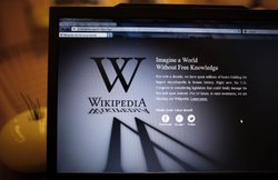 A laptop computer displays Wikipedia's front page showing a darkened logo on ...