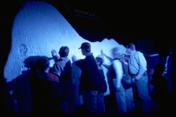 Visitors to the exhibit place their hands on the iceberg replica to gauge how...