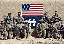Marines pose with a flag bearing a symbol resembling the Nazi SS emblem in Af...