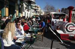 A tourist train passes diners in cafes beneath the Acropolis on February 19, 2012 in Athens, Greece.