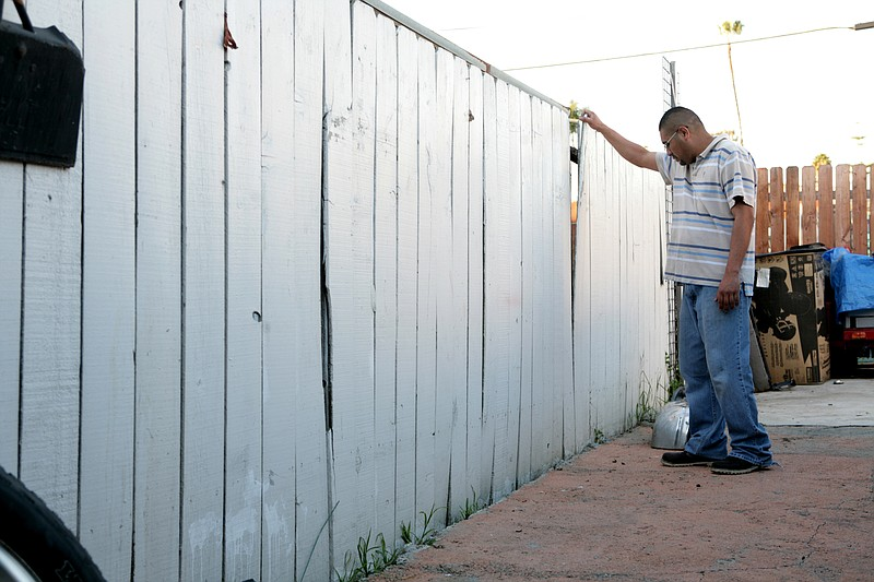 Alejandro Gonzalez shows where water from a ruptured water main rushed through his fence in December 2010, covering his patio and personal belongings in mud, on Wednesday, Feb. 22, 2012