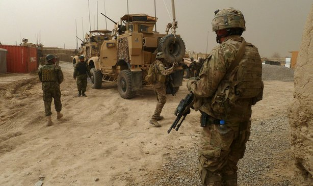 US soldiers keep watch at the entrance of a military base near Alkozai village following the shooting of Afghan civilians allegedly committed by a rogue US soldier in Panjwayi district, Kandahar province on March 11, 2012.