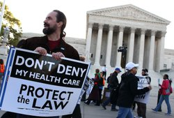 A protester stands outside the U.S. Supreme Court Building on March 26, 2012 ...