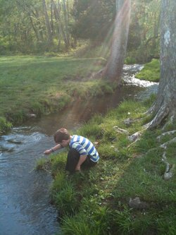 "A young boy plays outdoors by a creek in the film ""Mother Nature's Child: Growing Outdoors In The Media Age."""