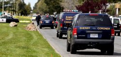 Sheriff coroner vans drive to the bodies of the shooting victims at Oikos Uni...