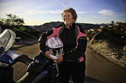 Nancy Fuller beams with joy after a ride on her motorcycle in Alpine.