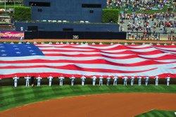 "Sailors assigned to the aircraft carrier USS Carl Vinson unfurl the ""Pacific Life Holiday Bowl Big Flag"" during pre-game activities at PETCO Park to commemorate the ninth anniversary of the Sept. 11, 2001 terrorist attacks on New York and Washington."