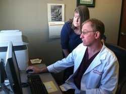 At Universal Pain Management, Dr. Francis Riegler confers with Trudy Roberts, the clinic's nurse practitioner, over a patient's record of prescription drug purchases.