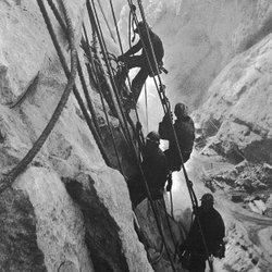 Of all the jobs required to build Hoover Dam, none was more dramatic and dangerous than that of the high scalers — men who swung from ropes 800 feet up, armed with dynamite and jackhammers, to blast and clean the canyon's walls and prepare them to take the dam's concrete.