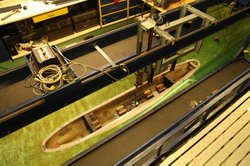 High angle shot of ship architectural model submerged in water tank.