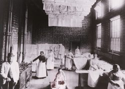 Archival photo of maids ironing and doing the laundry at Petworth House.