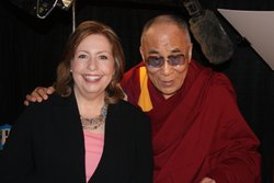 KPBS Midday Edition host Maureen Cavanaugh poses with the Dalai Lama during a...