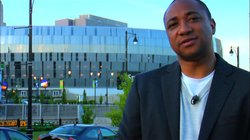 """Damon Gupta, host of """"The Next American Dream,"""" stands in front of the Sprint Center, Kansas."""