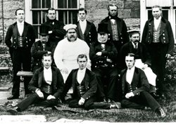 Archival photo of eleven indoor male servants with the chef at Petworth House.