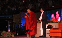 His Holiness the 14th Dalai Lama waves on stage with Elliot Hirshman, preside...