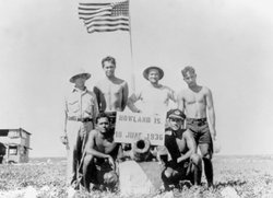 A group of colonists take a photo with the American flag on Howland Island, J...