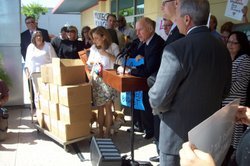 Gov. Jerry Brown, First Lady Anne Gust Brown and First Dog Sutter Brown show off boxes of signature petitions for the governor's proposed November tax initiative at the Sacrament County Elections Office Thursday.