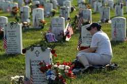 Denise Hlavaty leans on the head stone of her boyfriend Army Staff Sergeant S...