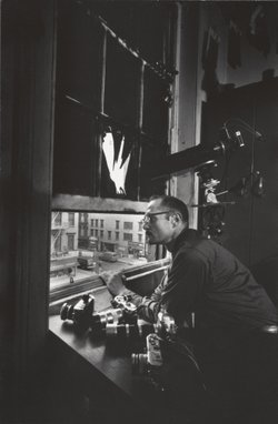 Photographer W. Eugene Smith at his fourth-floor window inside the Jazz Loft,...