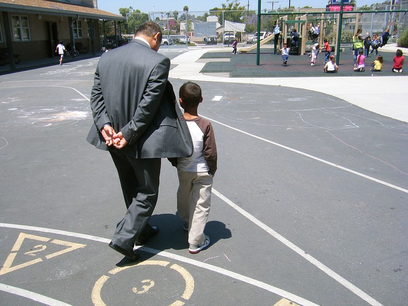 Cherokee Point Elementary School Principal Godwin Higa walks with a student o...