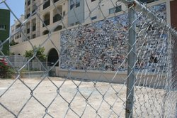 A photographic mosaic of life in City Heights faces a fenced-off vacant lot, ...