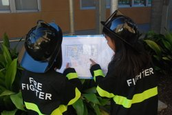 Two Joyner Elementary School students who work as fire fighters in the school's micro city review exit route maps.