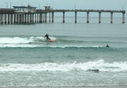 A surfer in Ocean Beach rides under the