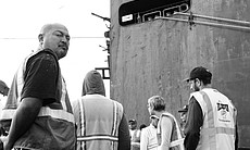 Longshoremen gather outside the Jinsei Maru for a safety briefing prior to offloading.