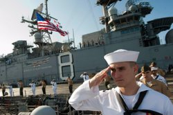 Sailors and Marines render a hand salute as the multi-purpose amphibious assa...