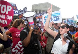 Local resident Angela Botlicella (R), along with other supporters, celebrate as they respond to the Supreme Court ruling on the Affordable Health Act June 28, 2012 in front of the U.S. Supreme Court in Washington, DC.