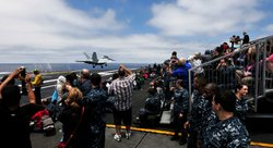 Sailors and guests observe an air-power demonstration from the flight deck of...