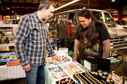 Picker Kevin Bruneau explores a vendor's table covered with jewelry on MARKET WARRIORS.
