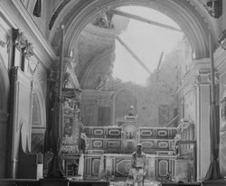 A private stands before a damaged altar in Acerno, Italy, on September 23, 1943.