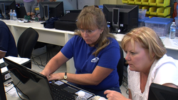 Lisa Barnett, a Rancho Bernardo teacher, debugs a computer program with her classmate at a San Diego State training program on July 16, 2012.