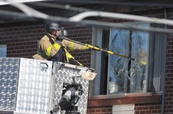 Police break the window of the apartment of of James Holmes, the suspect of a...