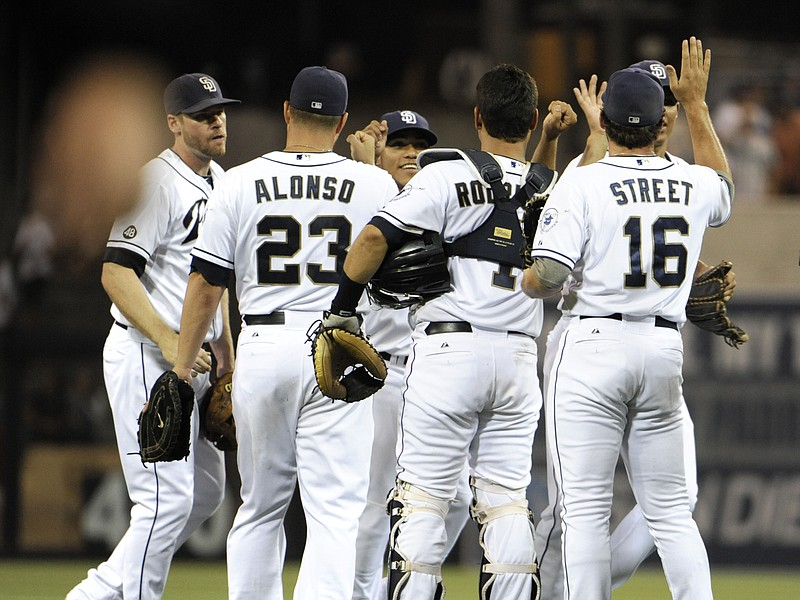 San Diego Padres players high-five after beating the Chicago Cubs 2-0 in a ba...
