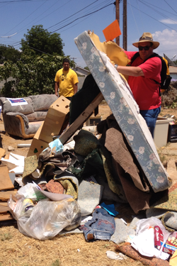 Community members remove trash from foreclosed property in the Mountain View neighborhood.
