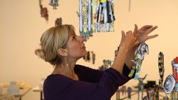 Artist Margaret Noble adjusts the hanging paper dolls of