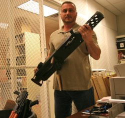 ATF Agent Peter Forcelli holds up the barrel of a .50-caliber rifle the agenc...