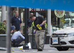 Law enforcement stands near the covered body of a suspected shooter on 5th Av...