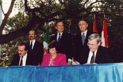 The NAFTA initializing ceremony in San Antonio, Oct. 7, 1992. Mexican President Carlos Salinas de Gortari and  United States President George H. W. Bush are top left, while U.S. Trade Representative Carla Hills is seated in the center.