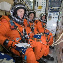 Seated on the middeck, astronauts Andrew J. Feustel (foreground), Michael J. Massimino and John M. Grunsfeld, all STS-125 mission specialists.